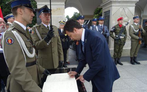 Marek Michalak wpisuje się do księgi pamiątkowej