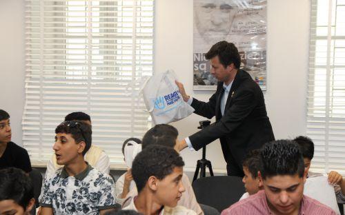 Rzecznik wręcza dzieciom torby z upominkami